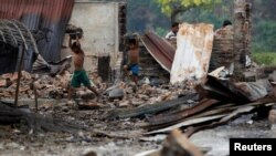 FILE - Children recycle goods from the ruins of a market which was set on fire at a Rohingya village outside Maugndaw in Rakhine state, Myanmar, Oct. 27, 2016.