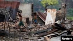 Anak-anak Rohingya mengumpulkan barang-barang yang masih bisa dipakai setelah sebuah pasar Rohingya di kota Maugndaw, Rakhine, Myanmar dibakar massa (27/10 /foto: ilustrasi).