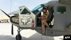 FILE - Afghanistan's first female pilot Niloofar Rahmani, 23, exits a fixed-wing Afghan Air Force aviator aircraft in Kabul, April 26, 2015.