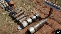 FILE - A Cambodian demining expert points to unexploded bombs displayed on the ground before a destruction ceremony organized by the Cambodia Mine Action Center (CMAC) at the complex of the Preah Vihear temple in Preah Vihear province.