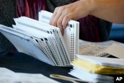 Seorang petugas pemilu menangani surat suara saat penghitungan suara di State Farm Arena pada Kamis, 5 November 2020, di Atlanta. (Foto: AP/Brynn Anderson)