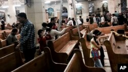 People look at damage inside a church in Tanta, Egypt, after a suicide bombing, April 9, 2017. Bombs exploded at two Coptic churches in the northern Egyptian cities of Tanta and Alexandria as worshippers were celebrating Palm Sunday, killing 45 people and wounding dozens more in assaults claimed by the Islamic State group. (AP Photo/Nariman El-Mofty)