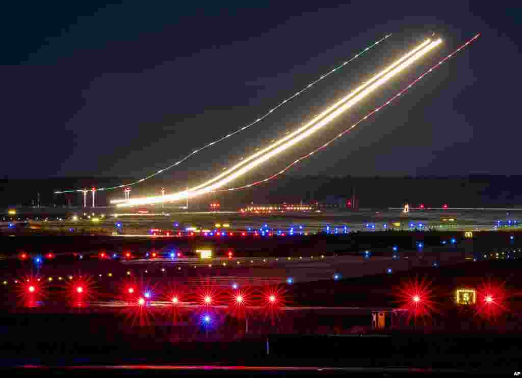 This long time exposure photo shows the lights of an aircraft while landing at the airport in Frankfurt, Germany.
