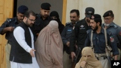 Pakistani officials escort famed Afghan woman Sharbat Gulla in a burqa or veil outside a court in Peshawar, Nov. 4, 2016.