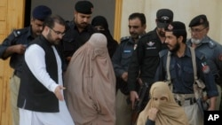 Pakistani officials escort famed Afghan woman Sharbat Gulla in a burqa or veil outside a court in Peshawar, Pakistan, Nov. 4, 2016.