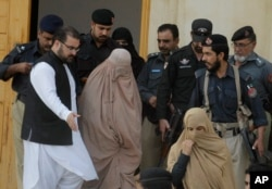 Pakistani officials escort famed Afghan woman Sharbat Gulla in a burqa or veil outside a court in Peshawar, Pakistan, Nov. 4, 2016.