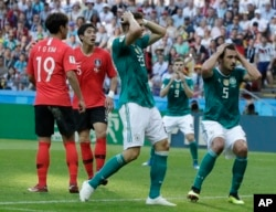 Germany's Mario Gomez, center, and Germany's Mats Hummels, right, hold their heads after failing to score during the group F match between South Korea and Germany, at the 2018 soccer World Cup in the Kazan Arena in Kazan, Russia, Wednesday, June 27, 2018.