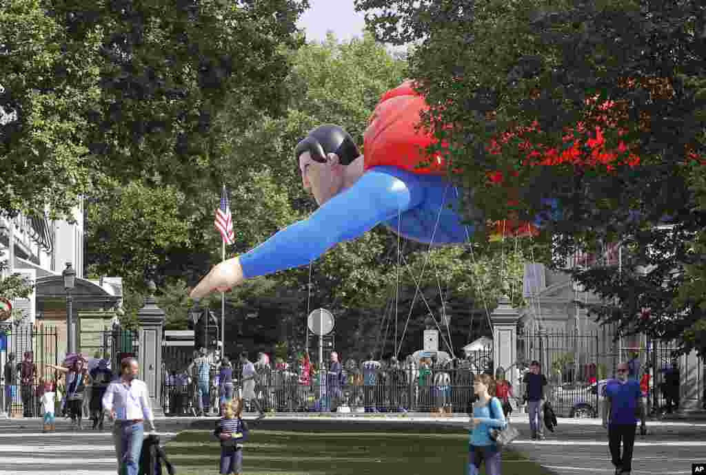 A giant inflatable Superman flies past the U.S. embassy during the Balloon Day Parade in Brussels, Belgium.