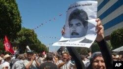 Para pendukung Mohammed Brahmi, berdemonstrasi menjunjung gambar politisi yang terbunuh pada hari Kamis (25/7) di Tunisia.