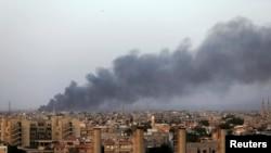 Asap mengepul di kota Benghazi akibat pertempuran antara militan Islamis dan pasukan Jenderal Khalifa Haftar (23/8). AS dan Eropa menentang campur tangan asing di Libya.