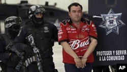Gilberto Barragan Balderas, right, is escorted by police officers as he is presented to the media in Mexico City, Friday, May 20, 2011