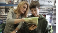 Augustine Sewell and his mother, Patricia, look at a Call of Duty: Black Ops video game that they purchased in Sacramento, California
