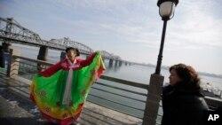 지난 2013년 2월 중국 접경도시 단둥에서 중국인 관광객이 한복을 입고 북한 신의주 쪽을 배경으로 사진을 찍고 있다. (자료사진)