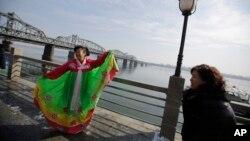 지난 2013년 2월 중국 접경도시 단둥에서 관광객들이 한복을 입고 북한 신의주 쪽을 배경으로 사진을 찍고 있다. (자료사진)