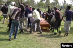 FILE - Mourners and fans of Kenyan musician Bernard Obonyo, whose stage name is Abenny Jachiga, carry his coffin away as they proceed his burial under the rules for the suspected COVID-19 cases, at Chiga village near Kisumu, Kenya, June 12, 2020.