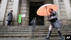 Una mujer pasa frente al Banco de Japón, el viernes, 29 de enero de 2016, cuando la institución introdujo tasas de interés negativas.