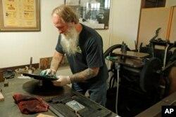 Loren Ackerman membersihkan tinta di mesin cetak untuk mencetak uang kayu di Tenino, Washington, 21 Mei 2020. (Foto: AP)