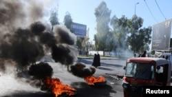 ລົດຕຸກຕຸກ ແລ່ນຜ່ານຢາງລົດທີ່ຖືກເຜົາໄໝ້ ໃນລະຫວ່າງ ການປະທ້ວງຕໍ່ຕ້ານລັດຖະບານ ໃນເມືອງເຄີບາລາ ຂອງອີຣັກ ທີ່ຍັງມີຢູ່ຕໍ່ເນື່ອງ, ວັນທີ 23 ທັນວາ 2019. REUTERS/Abdullah Dhiaa al-Deen