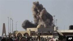 Anti-Gadhafi rebels run away as smoke rises following an air strike by Libyan warplanes near a checkpoint of the anti-Libyan Leader Moammar Gadhafi rebels, in the oil town of Ras Lanouf, eastern Libya, March 7, 2011