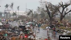 Residents walk on a road littered with debris after Super Typhoon Haiyan battered Tacloban city in central Philippines Nov. 10, 2013.