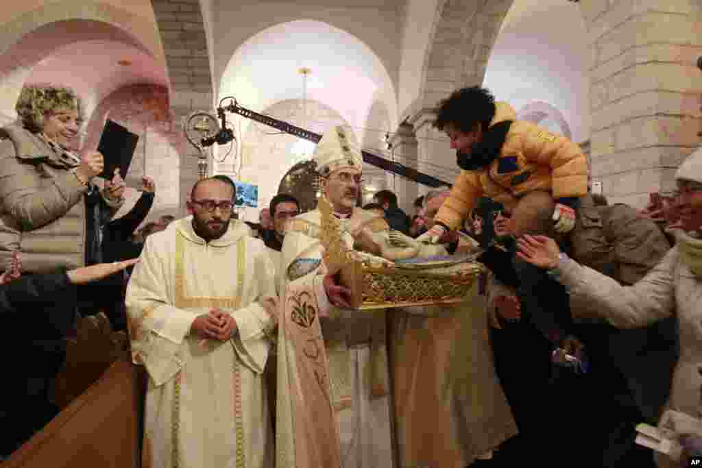 Archbishop Pierbattista Pizzaballa, center, apostolic administrator of the Latin Patriarch of Jerusalem, holds a statue of Baby Jesus in Saint Catherine's Church at the end of the Christmas Midnight Mass and walks in procession to the 'Grotto', where Christians believe the Virgin Mary gave birth to Jesus Christ, in the adjacent Church of the Nativity in Bethlehem, West Bank, Dec. 25, 2016.