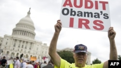 Demonstrators protest the Internal Revenue Service targeting of the Tea Party and similar groups during a rally outside the US Capitol in Washington, DC, June 19, 2013.