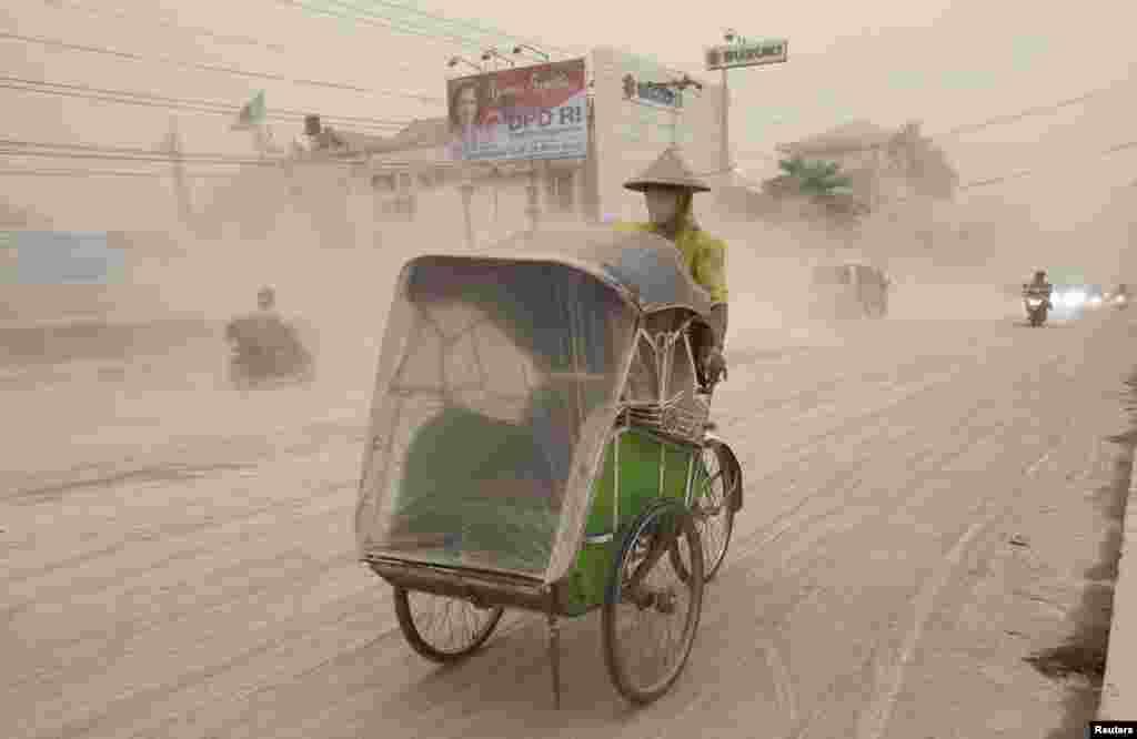 Seorang pengendara becak memakai masker di tengah hujan abu di Yogyakarta (14/2) yang berasal dari letusan Gunung Kelud. (Reuters/Dwi Oblo)