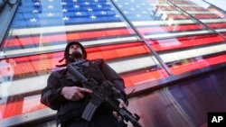FILE - A heavily armed New York city police officer with the Strategic Response Group stands guard at New York's Times Square, Nov. 14, 2015.
