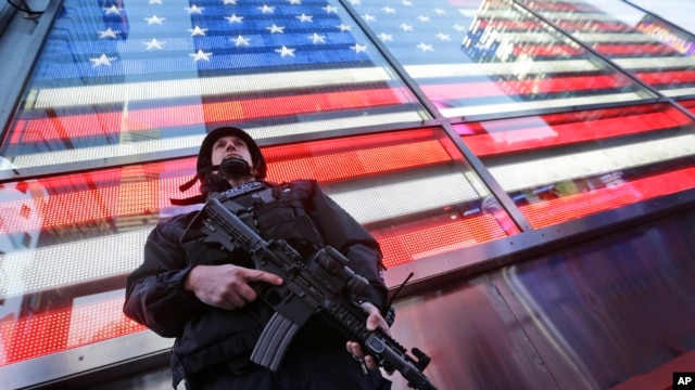 FILE - A heavily armed New York city police officer stands guard at the armed forces recruiting center in New York's Times Square, Nov. 14, 2015.