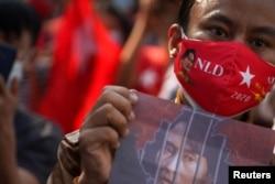 Manifestante sostienesostiene una foto de la líder Aung San Suu Kyi frente a la embajada de Birmania, el 1 de febrero de 2021.