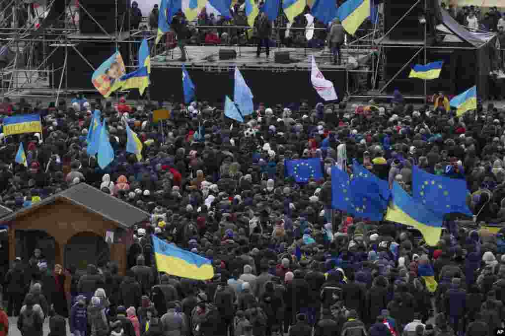 Para demonstran melambai-lambaikan bendera selama protes di Alun-Alun Independence di Kiev (2/12). (AP/Ivan Sekretarev)