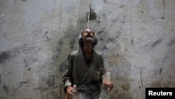 A man cools off from a public tap after filling bottles during intense hot weather in Karachi, Pakistan, June 23, 2015.