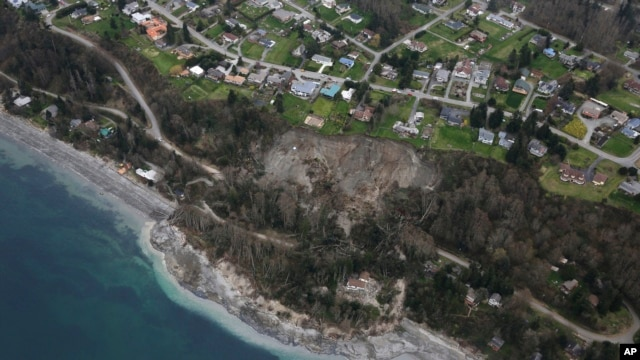 In this aerial photo, a landslide is shown near Coupeville, Wash. on Whidbey Island, Wednesday, March 27, 2013.   Whidbey Island authorities say one home has been severely damaged by the landslide that has isolated or threatened 33 more homes in the community overlooking Puget Sound about 50 miles north of Seattle.  Central Whidbey Fire and Rescue evacuated one person from the damaged home. About 10 more residents have been evacuated by boat.  (AP Photo/Ted S. Warren)