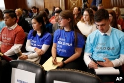 Attendees of a Senate Committee on Energy and Natural Resources committee hearing wear t-shirts protesting Interior Secretary Ryan Zinke, as he testifies before the committee about the President's Budget Request for Fiscal Year 2019, March 13, 2018, on Ca
