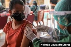 Seorang perempuan menerima satu dosis vaksin AstraZeneca COVID-19 saat program vaksinasi massal untuk Kawasan Wisata Hijau di Sanur, Bali, 23 Maret 2021. (Foto: REUTERS/Nyimas Laula)
