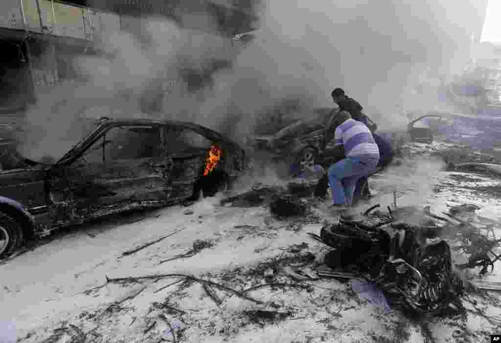 Two men remove a dead body from a burned car, after explosions near the Iranian embassy in Beirut, Nov. 19, 2013.