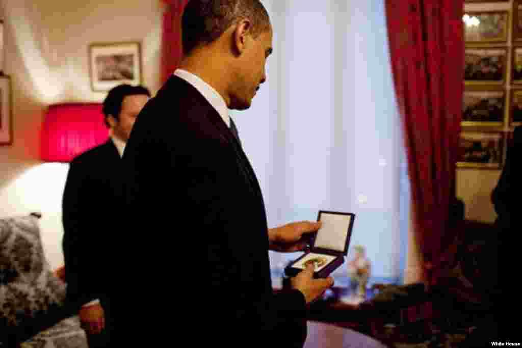 Le président Barack Obama examinant pour la première fois la médaille du Prix Nobel de la paix à l'Institut Nobel d'Oslo, en Norvége le 10 décembre 2009. (White House/Pete Souza)