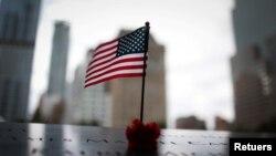 Sebuah bendera Amerika dan mawar merah di tepi selatan kolam refleksi 9/11 Memorial & Museum, menjelang peringatan 20 tahun serangan 9/11 di Manhattan, New York, AS, 8 September 2021. (REUTERS/Mike Segar)
