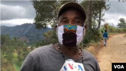 This Furcy resident, wearing a patchwork face mask, says locals make sunflower tea to soothe cold and flu-like symptoms. (Photo: Matiado vilme / VOA)