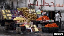 File - A vendor stands next to his fruit stall as he waits for customers near a mosque in Cairo.