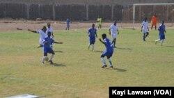 """Les équipes d'Athleta FC (blanc) et le club """"les amis du monde"""" (bleu) se rencontrent à Lomé, au Togo, le 18 mars 2017. (VOA/Kayi Lawson)"""