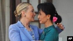 ຜູ້ນຳປະຊາທິປະໄຕມຽນມາ (ຂວາ) ກ່າວອຳລາ ຕໍ່ລັດຖະມົນຕີການຕ່າງປະເທດສະຫະລັດ ທ່ານນາງ Hillary Clinton ທີ່ໄປຢ້ຽມຢາມລຸນຫຼັງການພົບປະທີ່ບ້ານພັກຂອງທ່ານນາງອອງຊານຊູຈີໃນນະຄອນຢ່າງກຸ້ງ (2 ທັນວາ 2011)