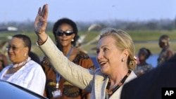 U.S. Secretary of State Hillary Clinton waves on arrival at Julius Nyerere International Airport in Dar es Salaam, Tanzania, June 11, 2011.