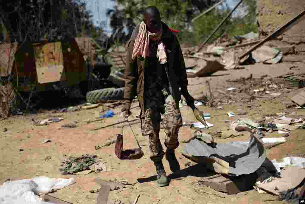 A Malian soldier walks inside a military camp used by radical Islamists and bombarded by French warplanes, in Diabaly, Mali, January 21, 2013.