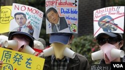 "Para pengunjuk rasa menggunakan ""masker"" dan membawa spanduk anti nuklir melakukan pawai di Tokyo (10/4)."