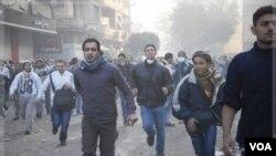 Para pengunjuk rasa berlarian saat terjadi bentrokan dengan aparat di Kairo, Mesir (23/11).