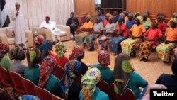 El presidente nigeriano Muhammadu Buhari (izquierda) habla a las 82 escolares Chibok liberadas por Boko Haram y llevadas a Abuja, Nigeria, el 7 de mayo.