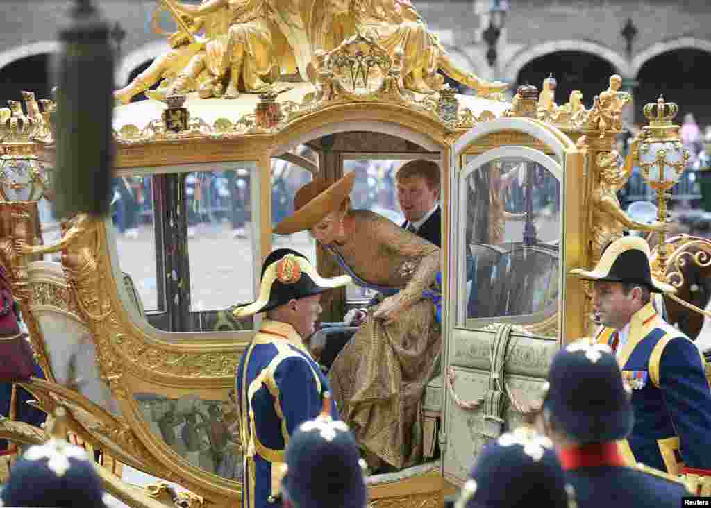 """King Willem-Alexander and Queen Maxima arrive at the 13th century """"Hall of Knights"""" in a horse-drawn carriage to officially open the new parliamentary year with a speech outlining the caretaker government's plan and budget policies for 2014, in The Hague, Netherlands."""