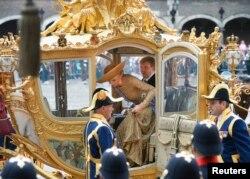 Rei Willem-Alexander e Rainha Maxima, descem da carruagem em referência, em Haia, 2014.