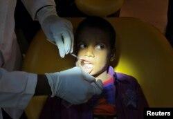 Seorang dokter memeriksa gigi geligi anak laki-laki berusia 7 tahun di sebuah rumah sakit di Chennai, India, 2 Agustus 2019. (Foto: Reuters)